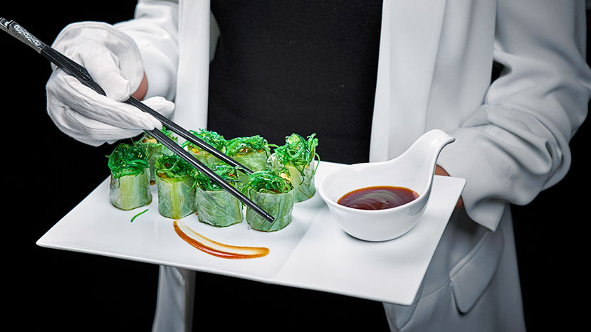 Спринг-роллы с начинкой из фунчозы и овощей украшены морскими водорослями чука и соусом хойсин